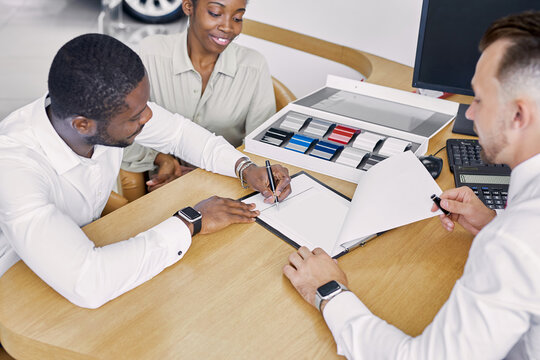 black clients sign a contract while sitting at table with salesman, professional worker of dealership explain terms of the contract and show where to sign