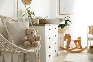 Stylish swing and changing table in baby room. Interior design
