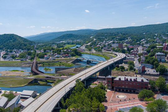 Interstate 68 passes through Cumberland, Allegany County, Maryland. A railroad bridge on the left crosses the Potomac River to Ridgeley, West Virginia.