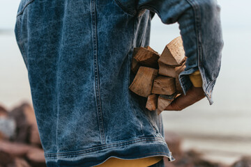 cropped view of man in denim jacket holding firewood