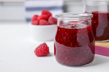 Delicious jam and fresh raspberries on white table, closeup. Space for text