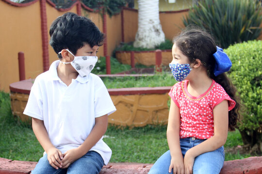 6-year-old Latino boys couple with face masks sitting waiting to play in times of covid-19