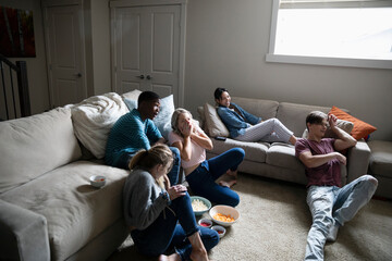 Teenagers hanging out, watching movie in living room