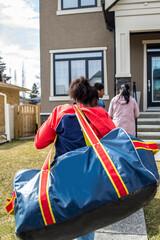 Teen girl returning home carrying hockey bag
