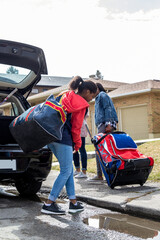Teen girl carrying sports bag from car