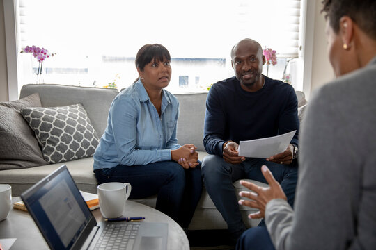 Financial advisor meeting with couple on living room sofa