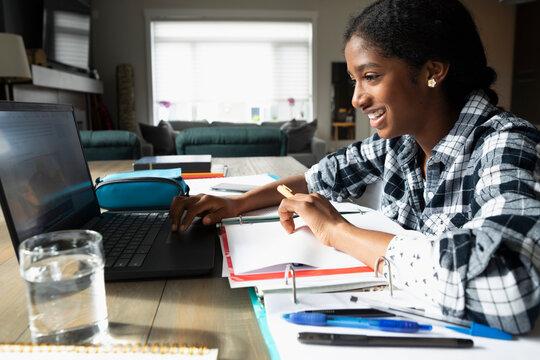 Smiling tween girl doing homework, using laptop at dining table