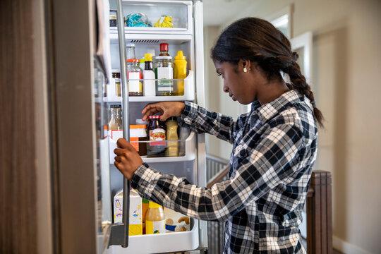 Preteen girl looking in refrigerator in kitchen