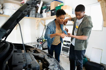 Mother teaching son how to change oil on car in garage