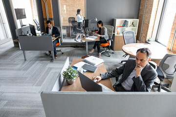 Focused businessman working at laptop in open plan office