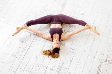 Supple young athlete doing a frontal split stretch