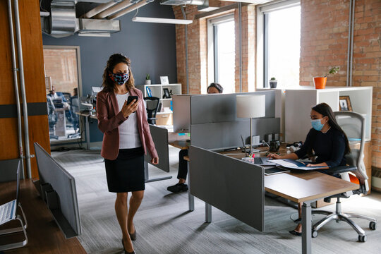 Businesswoman in face mask using smart phone in office
