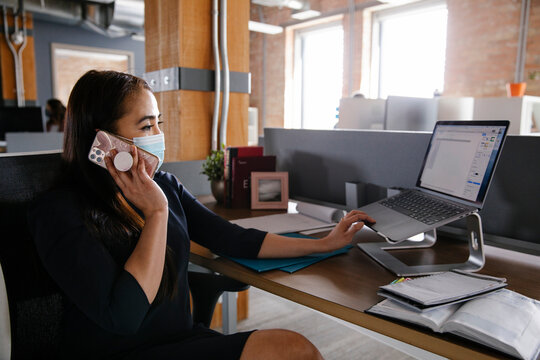 Businesswoman in face mask working at laptop in office