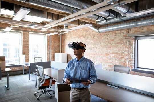 Businessman using VR simulator and digital tablet in new office