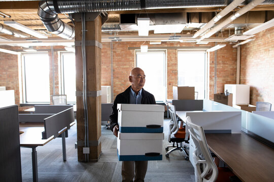 Businessman carrying boxes in new open plan office