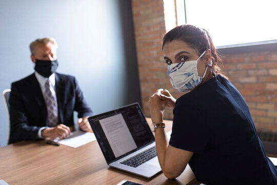 Portrait businesswoman in face mask in conference room meeting