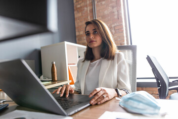 Businesswoman working at laptop and computer in office