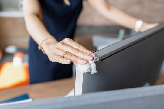 Businesswoman disinfecting computer in office