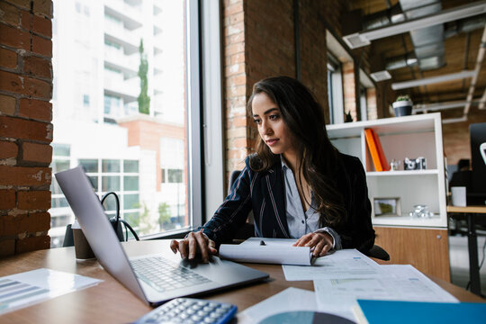 Young businesswoman working at laptop in office