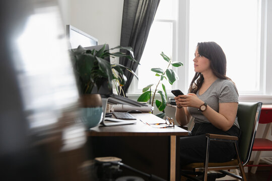 Young woman using phone in home office