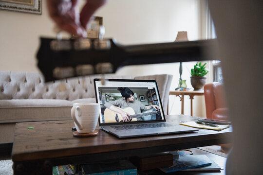 Man watching woman teaching guitar lesson on laptop