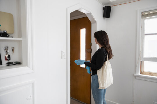 Woman wearing latex gloves leaving home