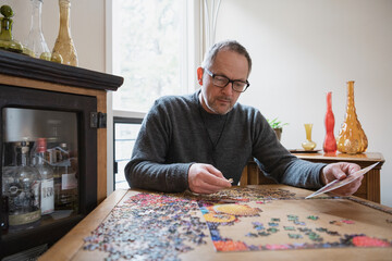Man assembling jigsaw puzzle on table at home