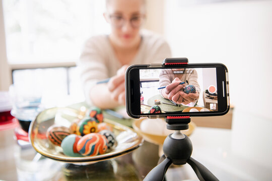 Young woman with smart phone vlogging Pysanka Easter egg decorating
