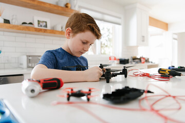 Boy assembling drone at kitchen counter