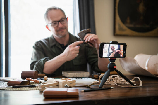 Man with smart phone vlogging leather crafting from home