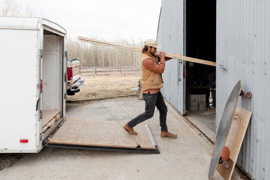 Male carpenter unloading wood from trailer at workshop
