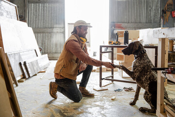 Male carpenter shaking hands with dog in woodworking workshop