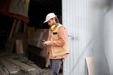 Male carpenter with smart phone taking a break outside workshop