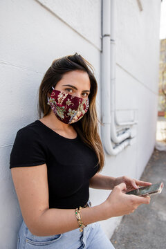 Young woman wearing face mask using phone by wall