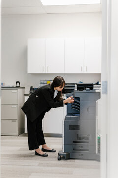 Young Asian woman using photocopier