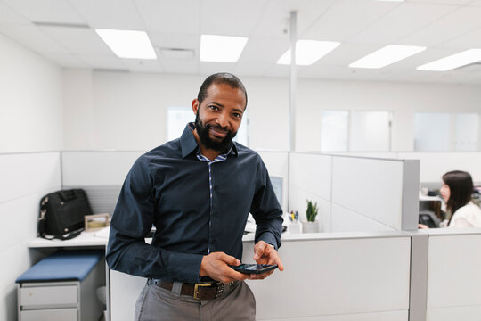 Mature man using phone in office