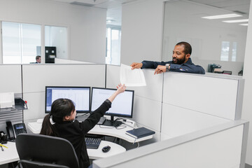Man handing woman document in office