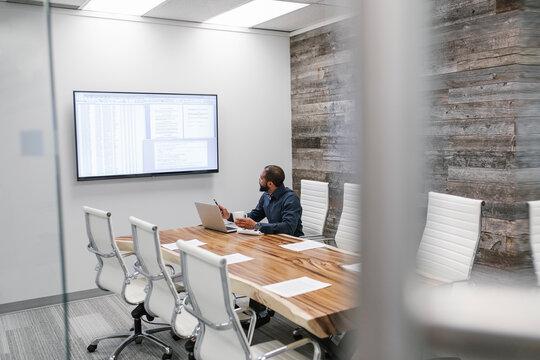 Mature man using laptop in meeting room