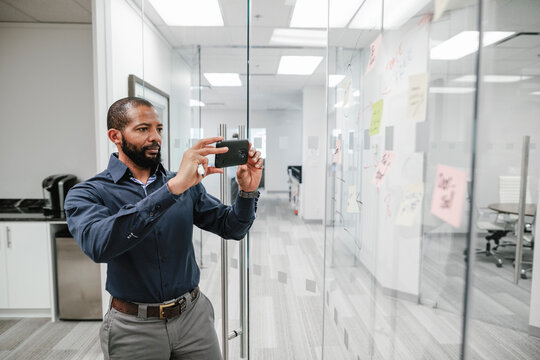 Man photographing sticky notes on window in office