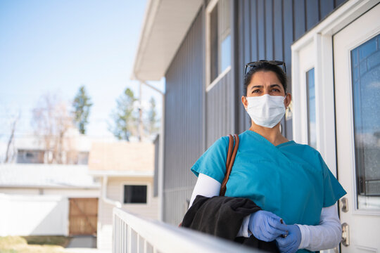 Female nurse in scrubs and face mask leaving house for work