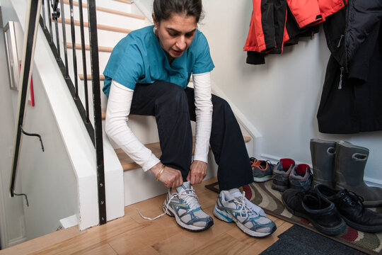 Female nurse in scrubs putting on sneakers at home