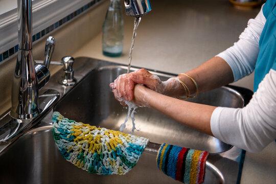Female nurse in scrubs washing hands at kitchen sink
