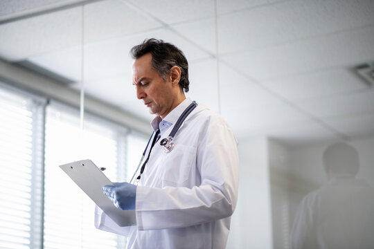 Medical researcher writing notes in laboratory