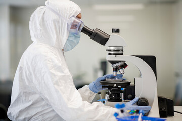 Medical researcher in PPE using microscope in laboratory