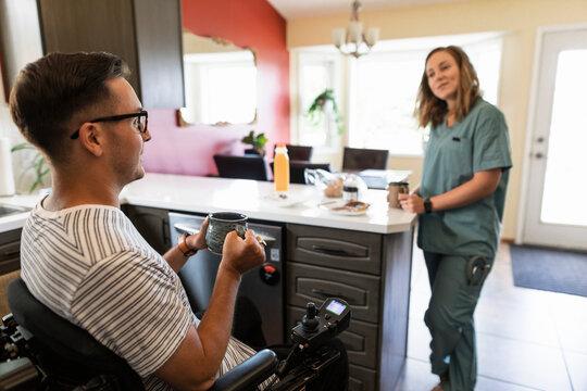 Quadriplegic man and medic girlfriend in scrubs having breakfast