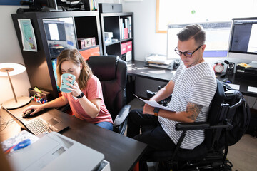 Quadriplegic man and girlfriend working together in home office