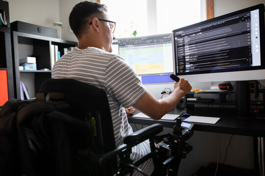 Man in wheelchair working at computer at home