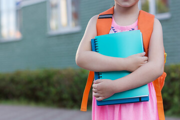 smart schoolgirl outdoors.Little student holds notebooks