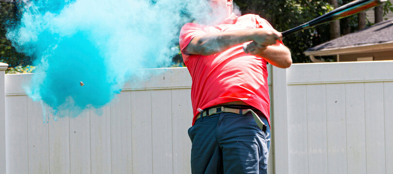 Its a boy revealed by father in pink shirt hitting a baseball with blue powder