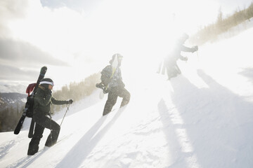 Skiers and snowboarder climbing sunny steep snowy mountain ski slope